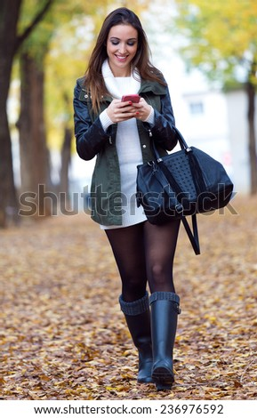 Outdoor portrait of beautiful girl walking with mobile phone in autumn.