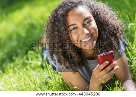 Outdoor portrait of beautiful happy mixed race African American girl teenager female young woman smiling with perfect teeth texting on cell phone - stock photo