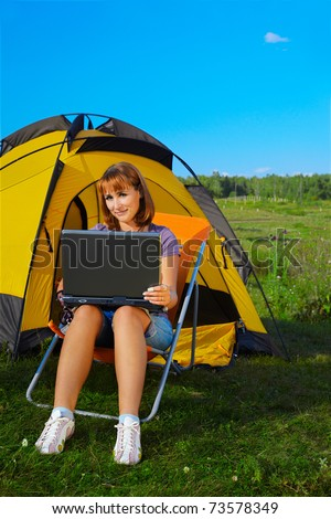 outdoor portrait of beautiful happy woman with laptop sitting in folding chair near camp tent - stock photo