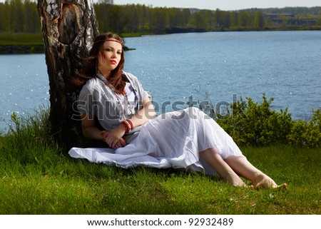 outdoor portrait of beautiful hippie girl sitting near birch. lake and forest on background - stock photo
