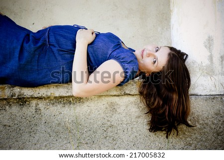 Outdoor portrait of beautiful pregnant woman holding her belly and posing by the old house - stock photo