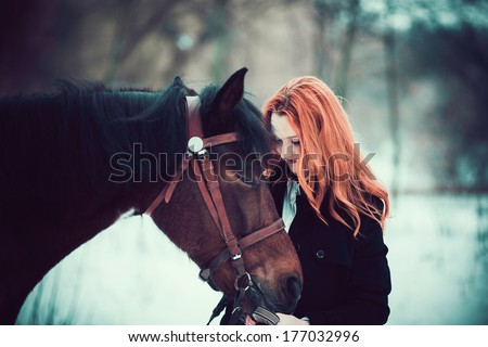 outdoor portrait of beautiful red haired girl with horse  - stock photo
