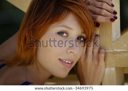 Outdoor portrait of beautiful red haired woman.