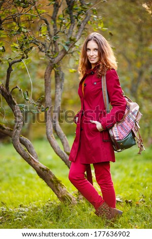 Outdoor portrait of beautiful redhead woman in red cloak with bag - stock photo