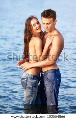 outdoor portrait of beautiful romantic couple of topless girl and muscular guy in jeans posing in sea waters