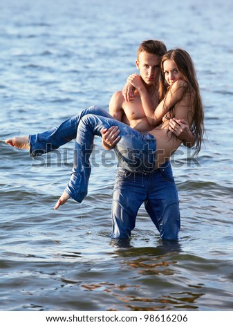 outdoor portrait of beautiful romantic couple of topless girl and muscular guy in jeans posing in sea waters. guy holds girl on hands