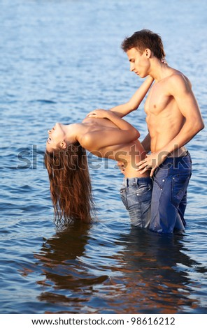 outdoor portrait of beautiful romantic couple of topless girl and muscular guy in jeans posing in sea waters - stock photo