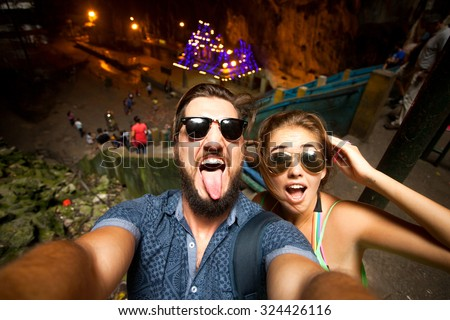 Outdoor portrait of beautiful traveling couple,hiker couple,hipster outfit,make selfie of their Asia trip,happy laughing couple,couple in sunglasses,emotional man and tongue girl,crazy selfie,hikers - stock photo