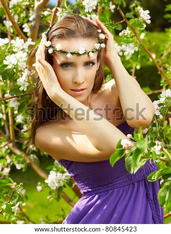 outdoor portrait of beautiful woman with fresh skin posing in garland near blooming apple tree