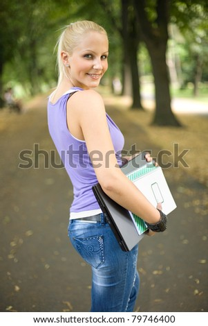 Outdoor portrait of beautiful young blond student girl holding exercise books and laptop. - stock photo