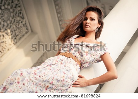 Outdoor portrait of beautiful young woman near column - stock photo