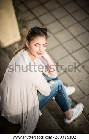 Outdoor portrait of beautiful young woman sitting on the stairs - stock photo
