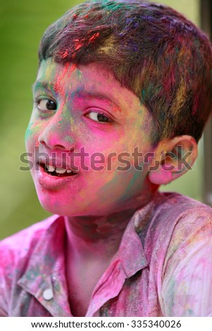 Outdoor portrait of boy with different colors on his face celebrates the Indian festival Holi - stock photo