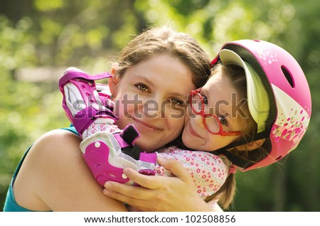 Outdoor portrait of caucasian mother and daughter wearing rollerblade protection and helmet. - stock photo