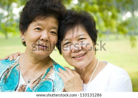 Outdoor portrait of cheerful asian women - stock photo
