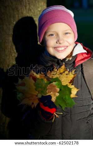 Outdoor portrait of cheerful smiling little girl with maple leaves - stock photo
