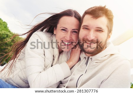 outdoor portrait of cheerful young adult couple looking at camera and smiling - stock photo