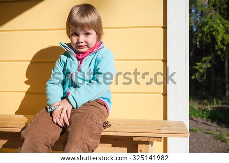 Outdoor portrait of confused Caucasian blond girl near rural wooden house wall