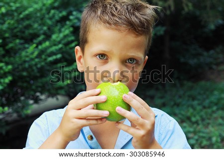 Outdoor portrait of cute boy eating an apple - stock photo