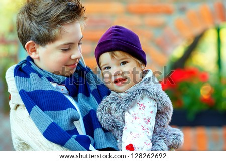 outdoor portrait of cute brother and sister - stock photo