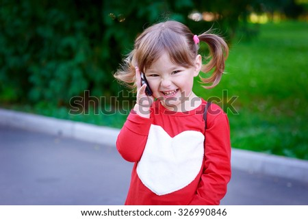 Outdoor portrait of cute little girl speaking by phone. - stock photo