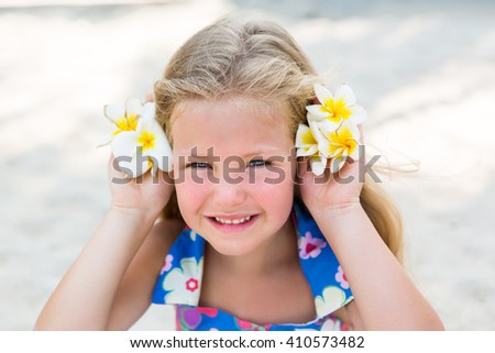 Outdoor portrait of cute small blonde girl in floral dress sitting on beach sand. Little lady smile and hold frangipani tropical flowers as a head hair ornaments. Summer sunny day. Happy Mothers day. - stock photo