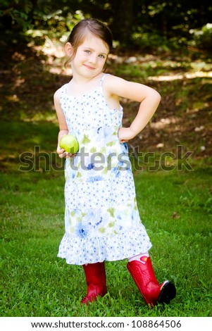 Outdoor portrait of cute young girl holding apple for healthy snack  in park - stock photo