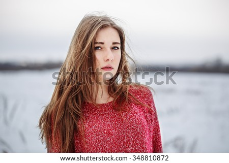 outdoor portrait of cute young pretty attractive serious girl with long dark hair red warm sweater on natural cloudy background in field. Outdoor winter photo in soft light. Lifestyle - stock photo