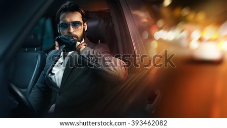 Outdoor portrait of elegant man driving a car