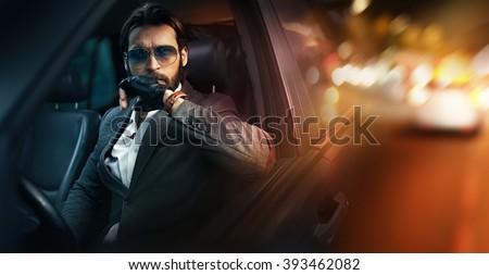 Outdoor portrait of elegant man driving a car - stock photo