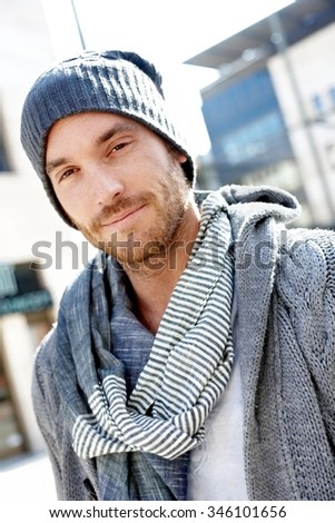 Outdoor portrait of goodlooking stylish guy standing, wearing scarf and smiling at camera. - stock photo