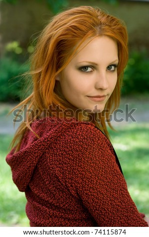 Outdoor portrait of gorgeous young redhead girl in the park.