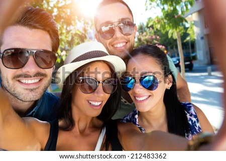 Outdoor portrait of group friends taking photos with a smartphone. - stock photo