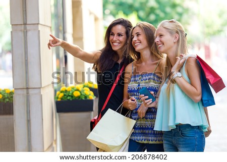 Outdoor portrait of group of beautiful girls looking at the shop window.  - stock photo
