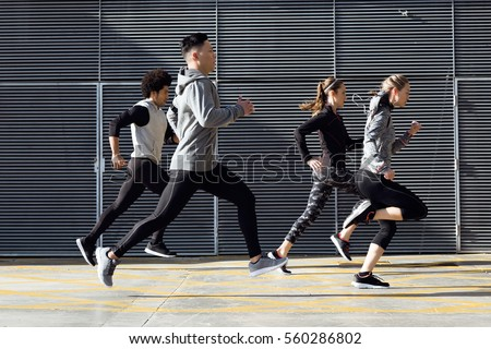 Outdoor portrait of group of friends running in the city.