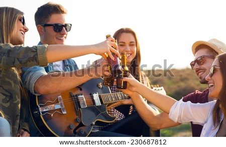 Outdoor portrait of group of friends toasting with bottles of beer. - stock photo