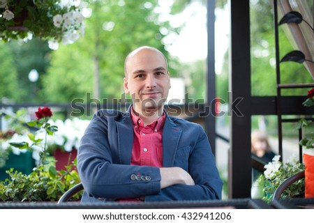 outdoor portrait of handsome fashionable bald man looking at camera - stock photo