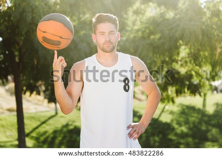 Outdoor portrait of handsome young man playing basketball on court.
