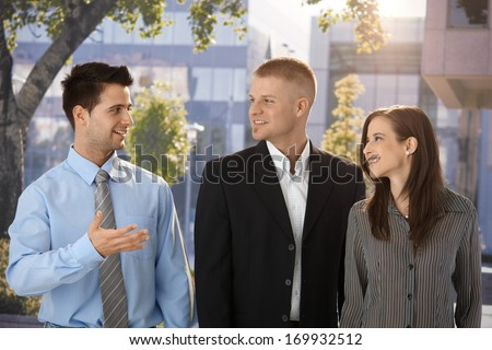 Outdoor portrait of happy businesspeople, standing in front of office building.