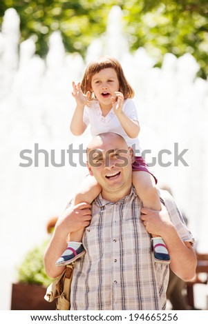Outdoor portrait of happy father with baby girl - stock photo