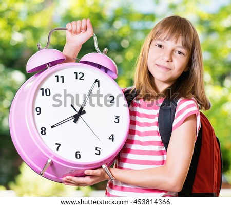 Outdoor portrait of happy girl 10-11 year old with big alarm clock and backpack. Back to school concept. - stock photo