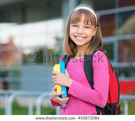 Outdoor portrait of happy girl 10-11 year old with book and backpack. Back to school concept. - stock photo