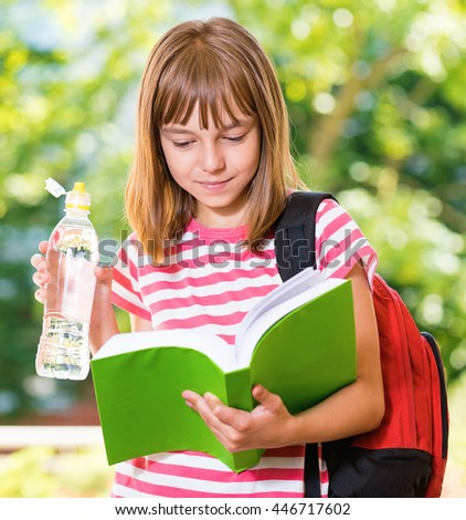 Outdoor portrait of happy girl 10-11 year old with book, schoolbag and bottle of fresh water. Back to school concept.