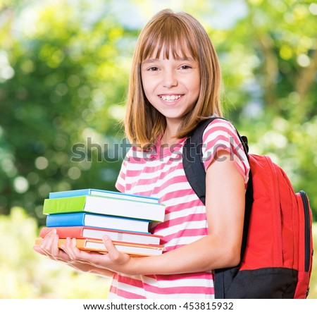 Outdoor portrait of happy girl 10-11 year old with books and backpack. Back to school concept. - stock photo