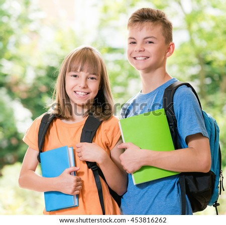 Outdoor portrait of happy teen boy and girl with books. Back to school concept. - stock photo