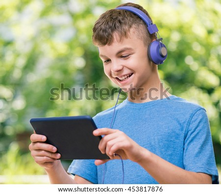 Outdoor portrait of happy teen boy 12-14 year old in headphones with tablet. Schoolboy watching media content in a tablet at park. - stock photo