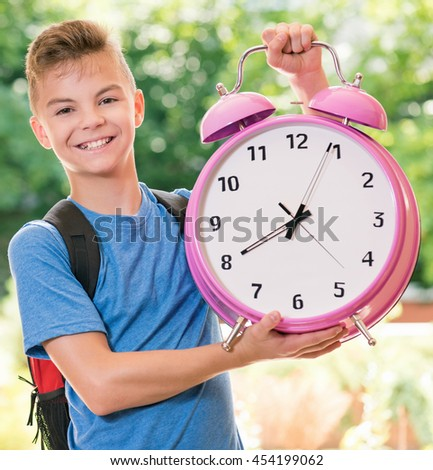 Outdoor portrait of happy teen boy 12-14 year old with big alarm clock. Back to school concept. - stock photo