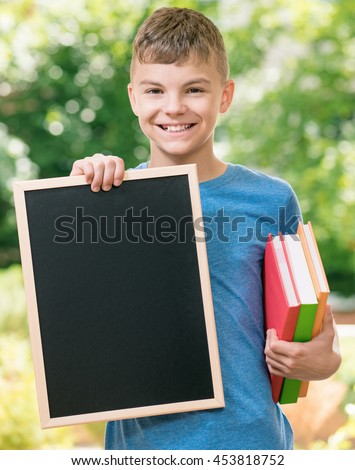 Outdoor portrait of happy teen boy 12-14 year old with small blackboard and books. Back to school concept. - stock photo