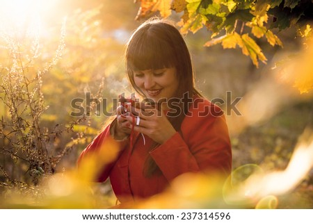 Outdoor portrait of happy woman drinking hot tea at autumn park - stock photo