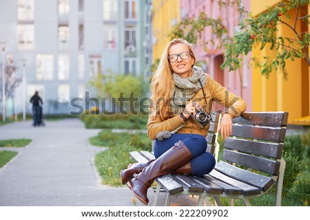 Outdoor portrait of hipster caucasian smiling girl sitting on the bench with retro photo camera in her hand - stock photo